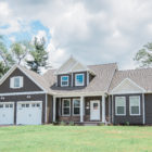large 1.5 story home with brown siding